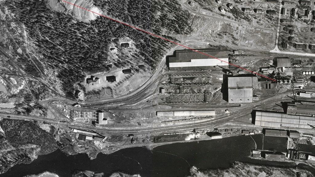 Flygbild äver hyttan, kolhuset och slaggtippen. Ett rött streck markerar linbanans väg